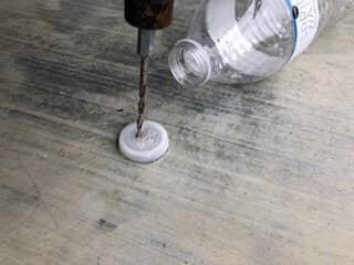 Drill holes in bottle cap for water irrigation