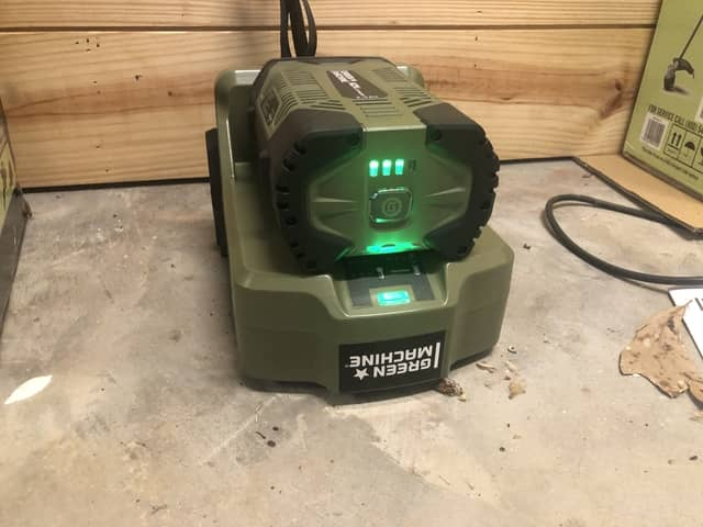 Green Machine charger being used to charge the 62v battery. A green light on the charger blinks while charging.